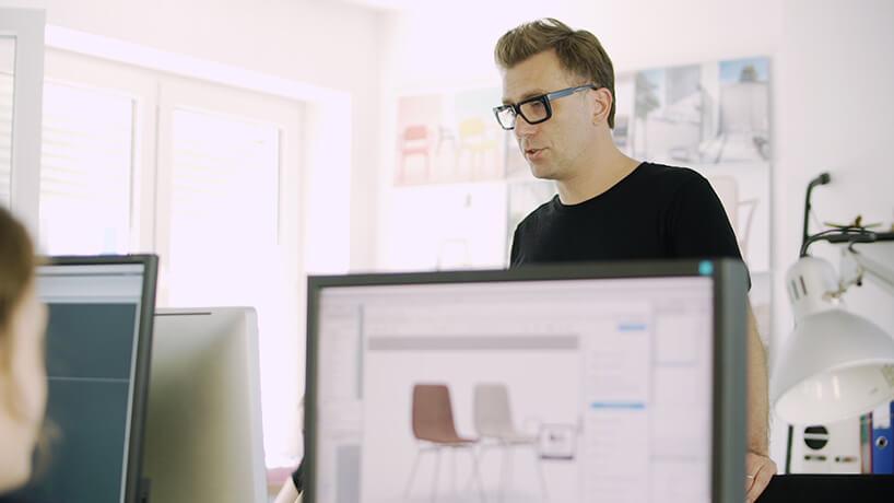Tomek Rygalik wtle podczas projektowania na komputerach