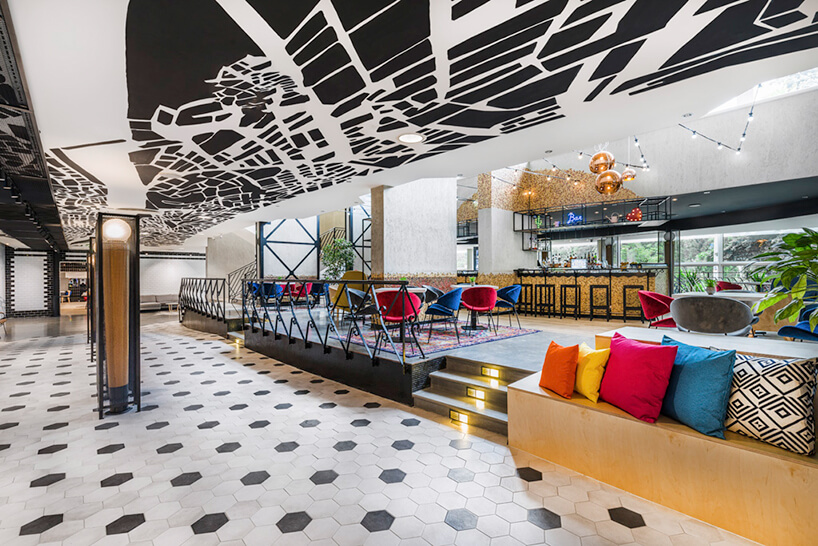 wnętrze hotelu Mercure Budapeszt od Tremend bar na podwyższeniu zkolorowymi krzesłami przy małych stolikach