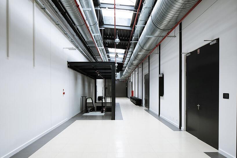 jasne korytarz wprzestrzeni pofabrycznej zciągami srebrnych rur wentylacyjnych
