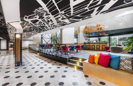 wnętrze hotelu Mercure Budapeszt od Tremend bar na podwyższeniu z kolorowymi krzesłami przy małych stolikach