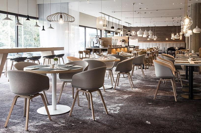 beżowe krzesła ibiałe stoliki weleganckiej restauracji