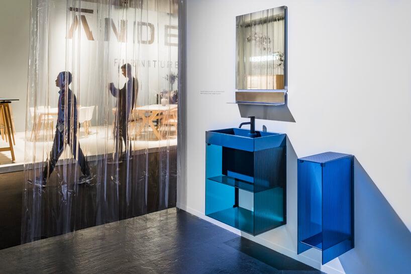 niebieskie przeźroczyste meble łazienkowa na białej ścianie na tle odwiedzających
