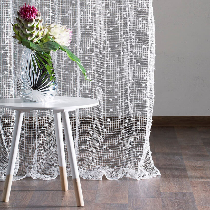 kwiaty wwazonie na białym stoliku na tle firanki