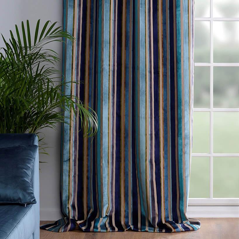 długa kolorowa zasłona obok niebieskiej sofy