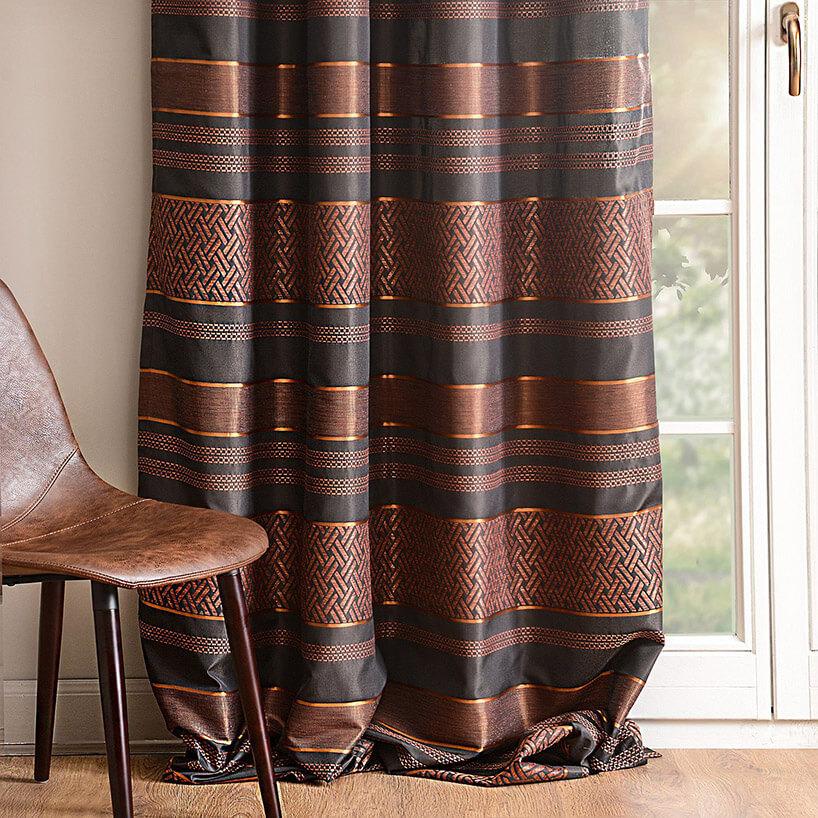 bordowe zasłony obok drewnianego krzesła
