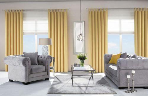 żółte zasłony w pomieszczeniu z szarymi meblami