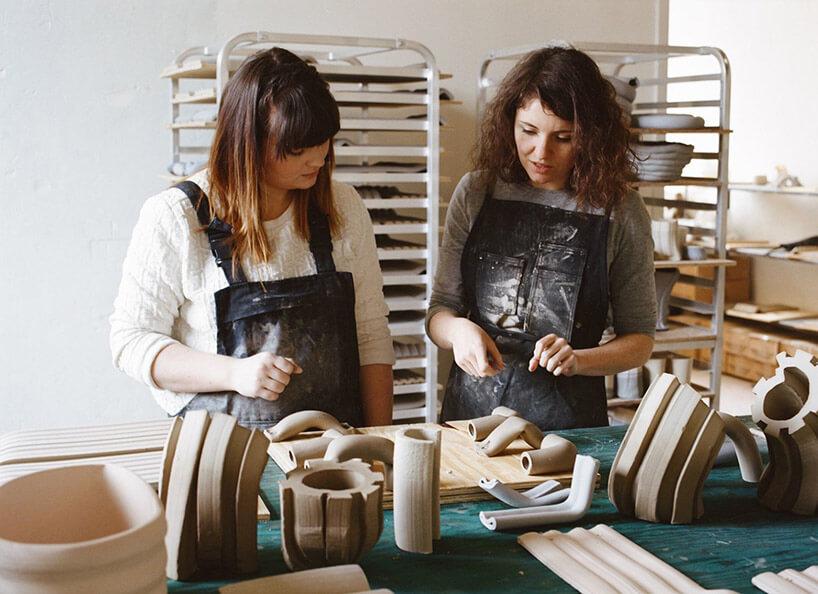 dwie kobiety stojące przy stole rzemieślniczym