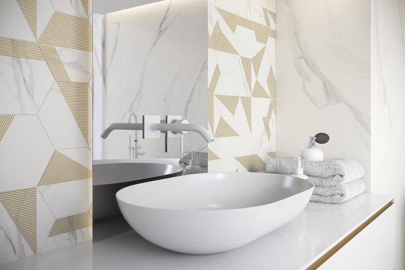 biała łazienka ze złotmi akcentami wpłytkach zbiałą umywalką zwkomponowanym wduże lustro kranem