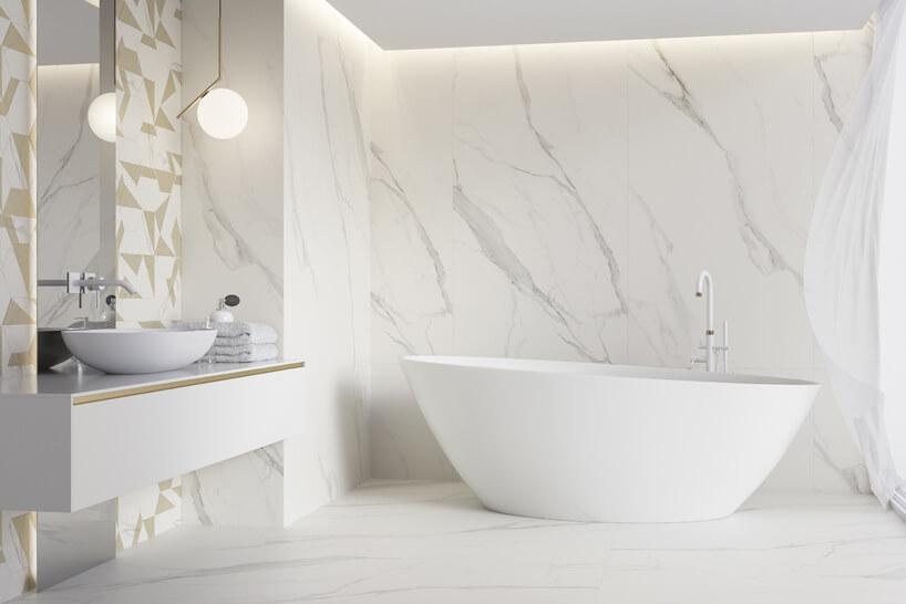 łazienka zdużą wolnostojącą wanną na tle jasnych kamiennych płytek