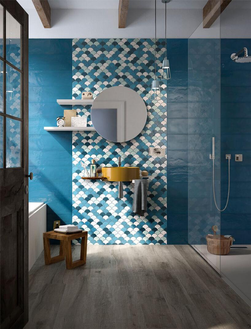 wyjątkowa niebieska łazienka zowalnymi płytkami za lustrem iżółtą umywalką
