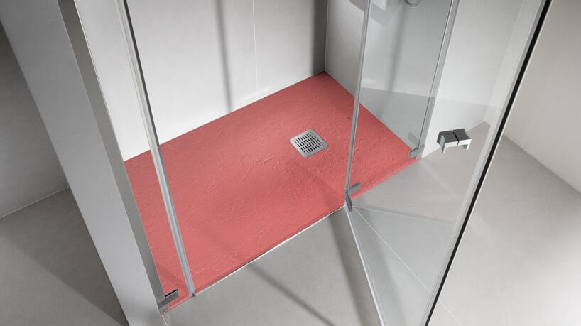 różowa podłoga pod natryskiem otoczona szarymi kafelkami