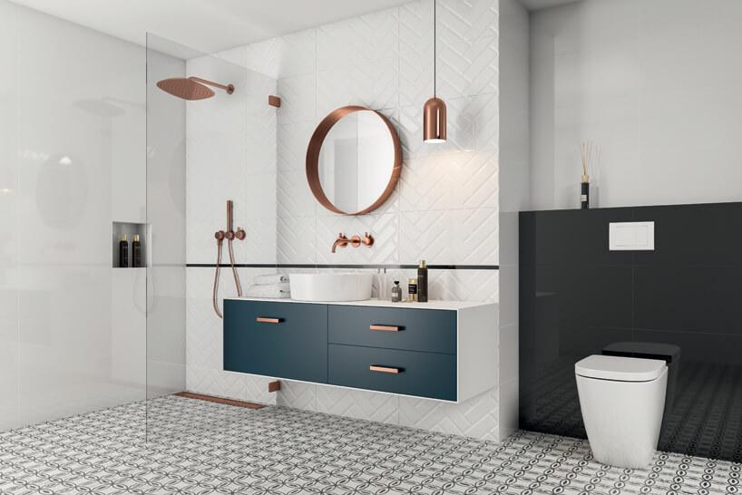jasna łazienka zgranatowymi frontami szafek iwykończeniami wraz zarmaturą wmiedzianym kolorze