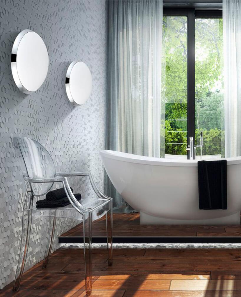 nowoczesna łazienka zszarą ścianą 3D wolnostjącą wanną iplastikowym przeźroczystym krzesłem