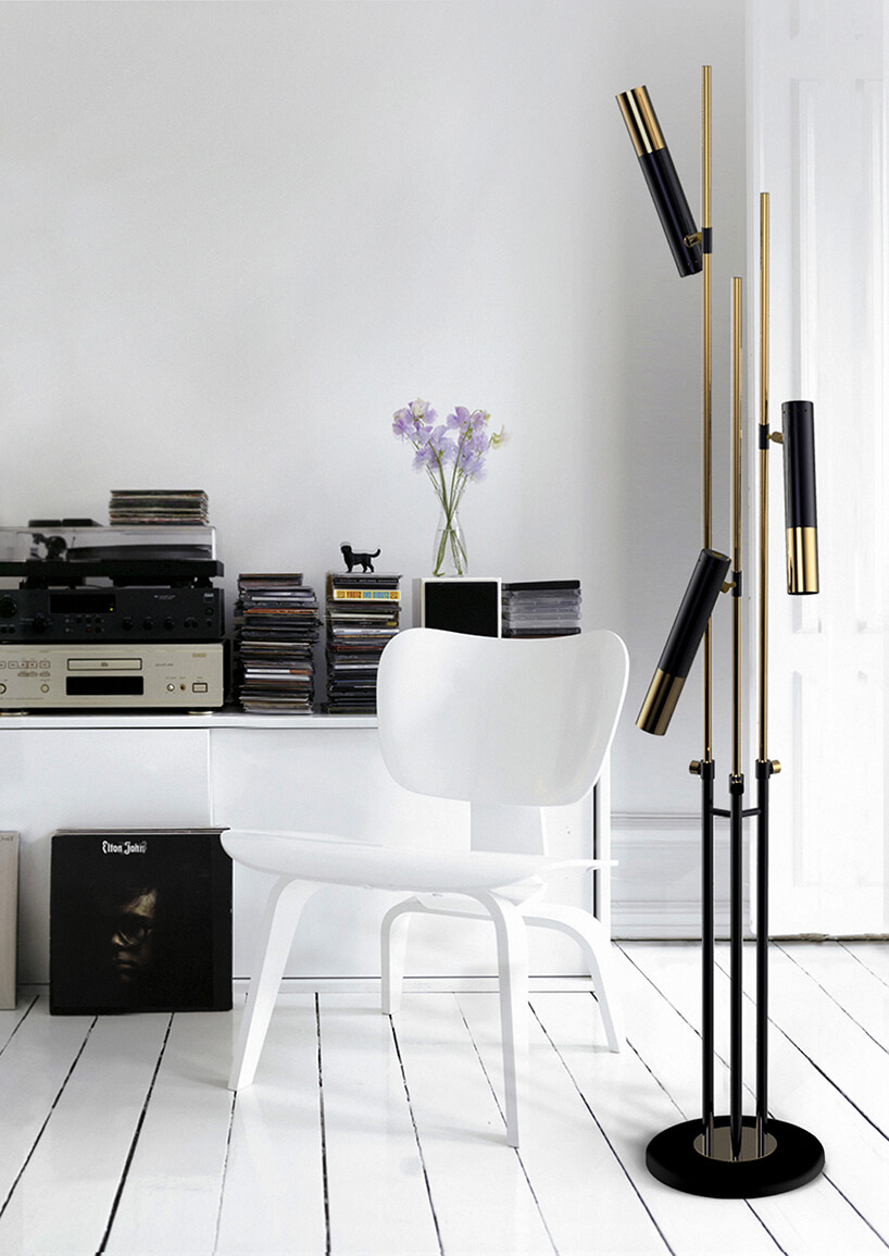 białe wnętrze salonu zwyjątkową czarną stojąca lampą ze złotymi elementami
