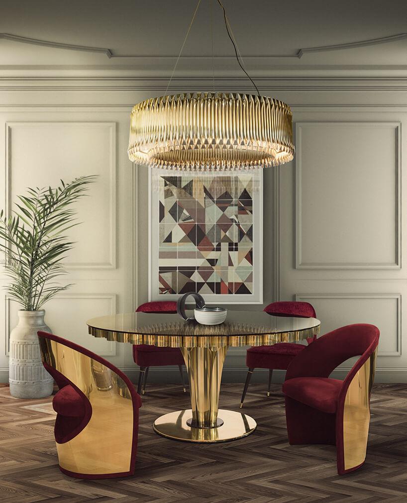 elegancka aranżacja wnętrza zokrągłym złotym stołem idwoma czerwono-złotymi fotelami pod dużym złotym żyrandolem