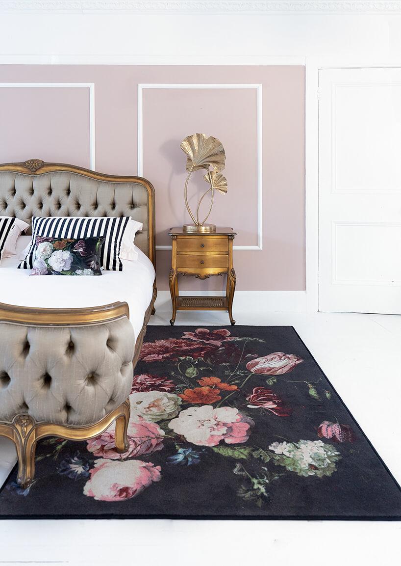 eleganckie drewniane łóżko ze złotymi wykończeniami iobite szarą skórą obok starego drewnianego stolika ze złotą lampą