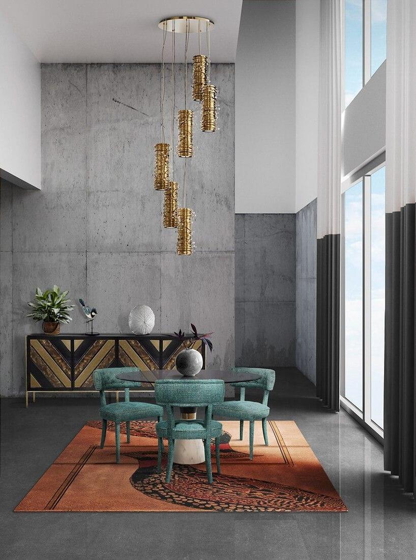 proste wnętrze zbetonową ścianą złotą wiszącą lampą nad czarnym stolikiem ztrzema zielonymi krzesłami