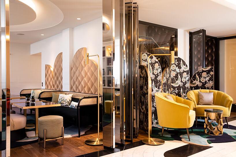 wnętrze wstylu glamour ze złotymi dodatkami iżółtymi fotelami przed małym złotym stolikiem