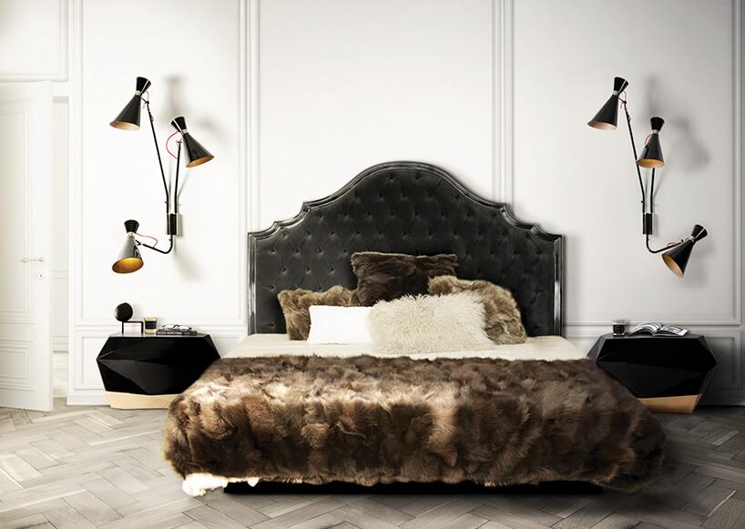 eleganckie czarne łóżko znarzutą zfutra obok czarnych szafek na tle białej ściany zlampami na ścianie