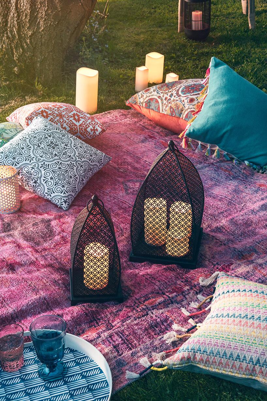 styl marokański czarne eleganckie lampiony na fioletowej narzucie zpoduszkami na trawie