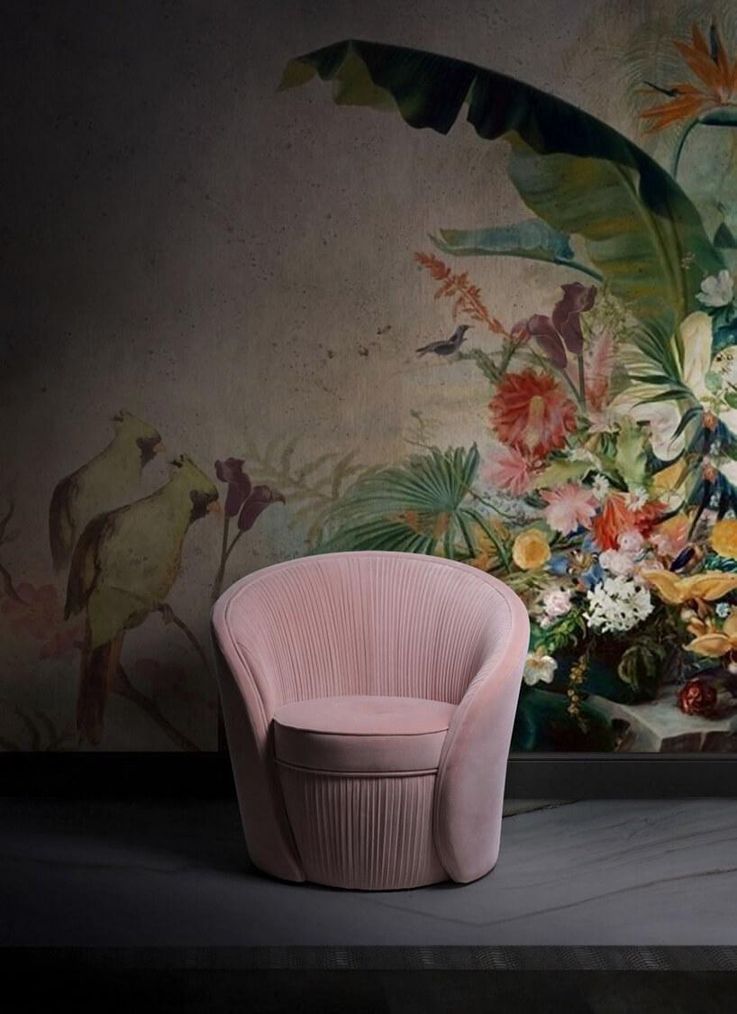 różowy fotel na tle ściany zroślinym motywem
