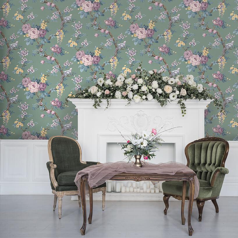 elegancki drewniany stół zdwoma klasycznymi fotelami na tle białego kominka na ścianie zmotywem kwiatów Magnolii