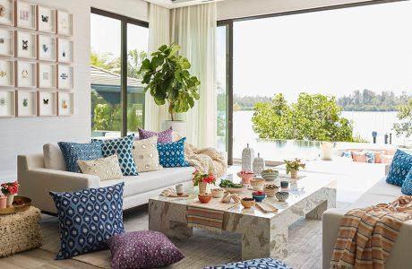 nowoczesna aranżacja wnętrza z niskim kamiennym stołem i dwoma sofami z poduszkami na tle wyjścia na basen zewnętrzny