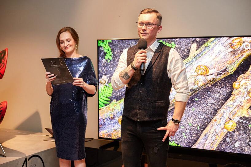 mężczyzna zmikrofonem Kamil Maślanka podczas prezentacji obok kobiety wniebieskiej sukience