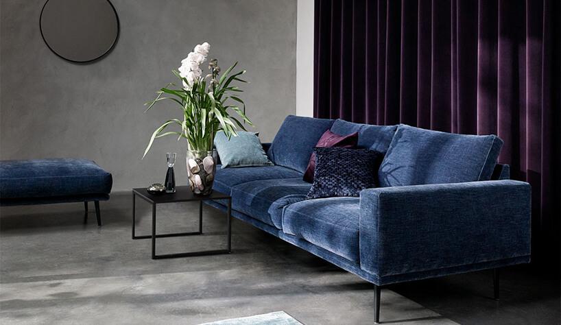 ciemno niebieska sofa na tle fioletowych zasłon
