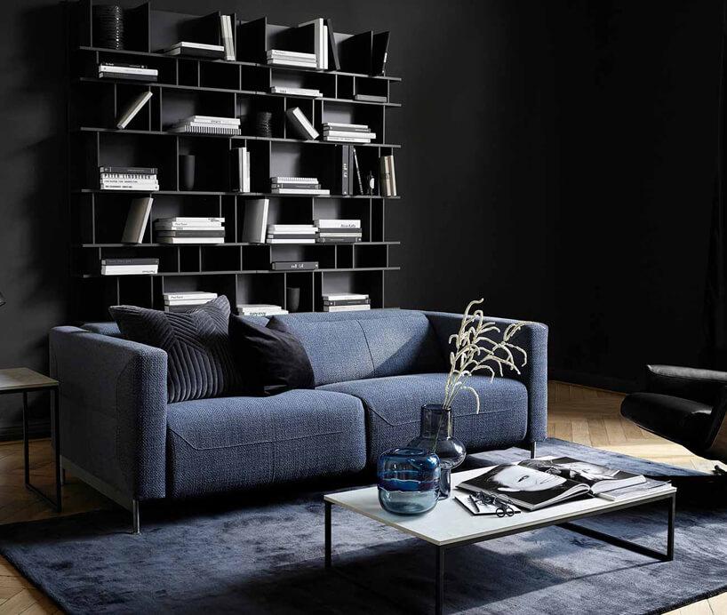 czarne wnętrze zpółką zksiążkami iniebieską sofą