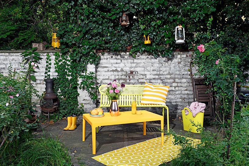 żółte nowoczesne meble ogrodowe ławka istoli na tle białego starego murku