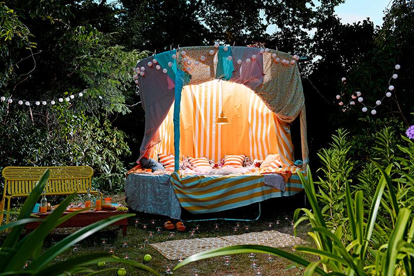 duża trampolina przykryta różnymi materiałami izrobionymi baldachimami przerobiona na sypialnię