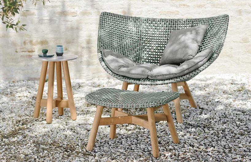 elegancki zestaw Mbrace od Dedon fotel ipodnóżek zdrewnianą kostrukcją iszarym plecionym siedziskiem obok małego drewnianego stolika