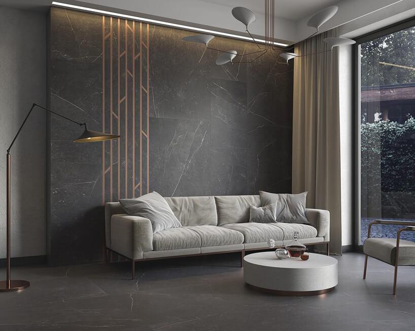 szara kanapa zpoduszkami istolik na tle ciemnej ściany