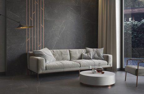 biała sofa na tle ciemnych płytek ze złotym akcentem z Paradyża