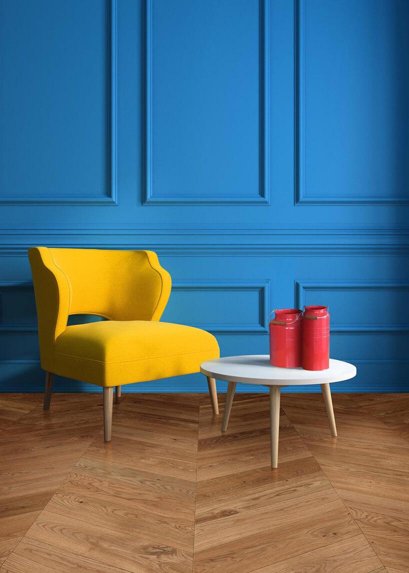 żółty fotel na drewnianej podłodze na tle niebieskiej ściany