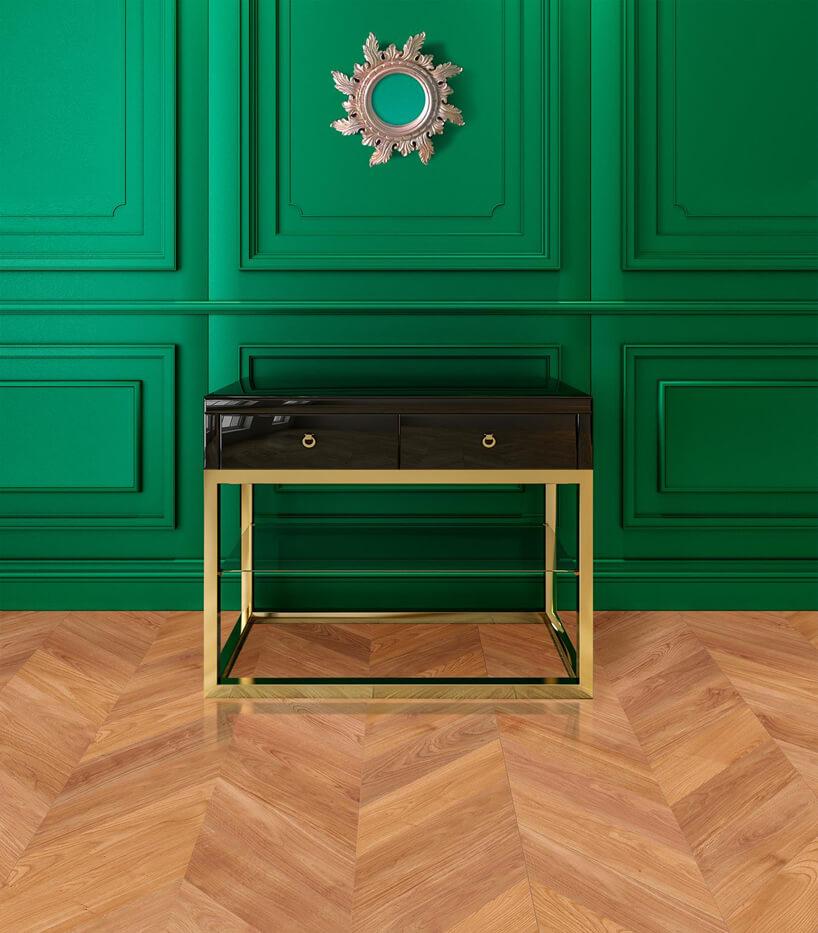 ciemna szafka na złotym stelażu na drewnianej podłodze na tle zielonej ściany
