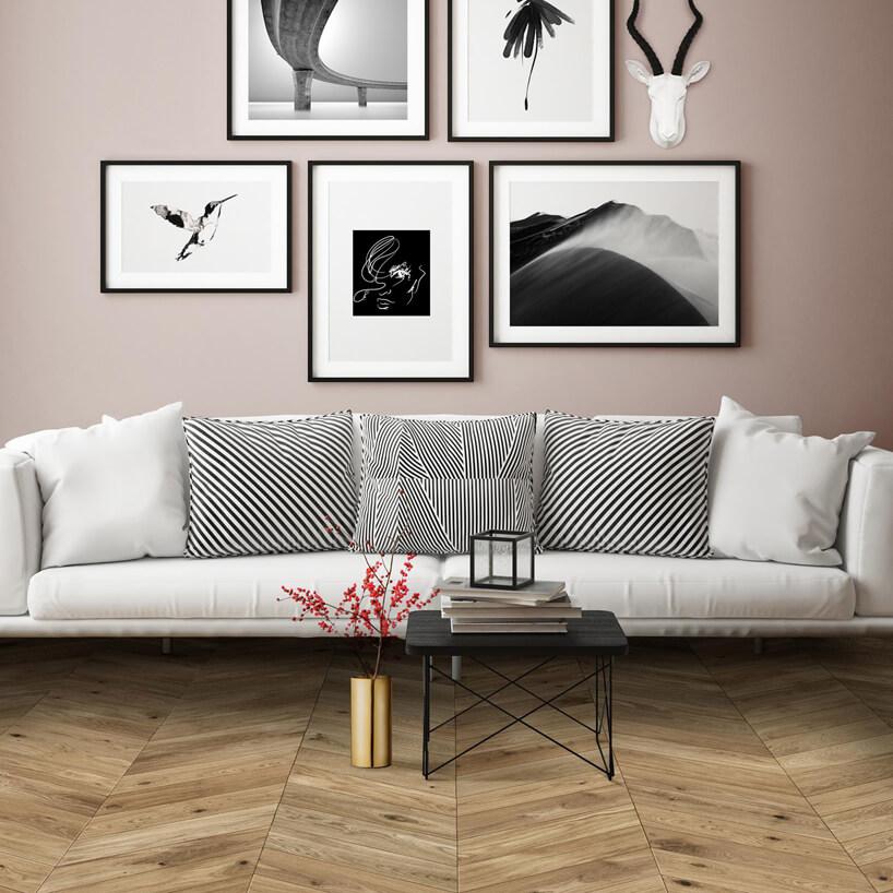 duża biała sofa na drewnianej podłodze na tle beżowej ściany zobrazami