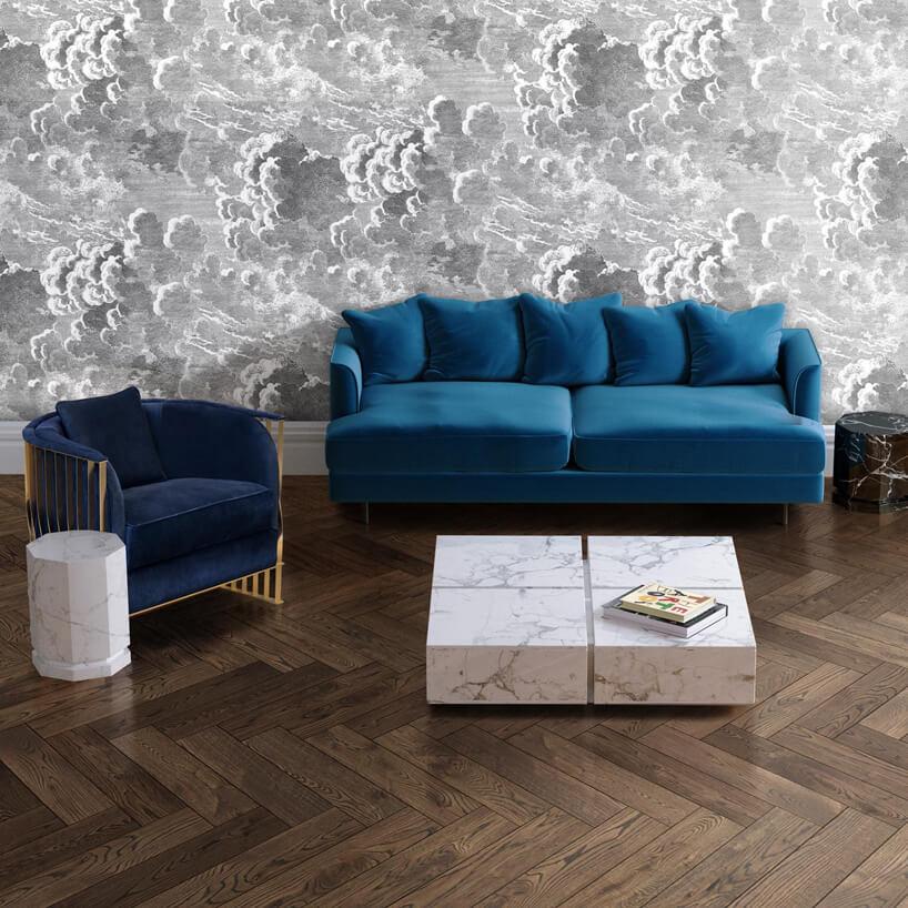 ciemna drewniana podłoga zniebieską sofą ifotelem przy niskim toliku