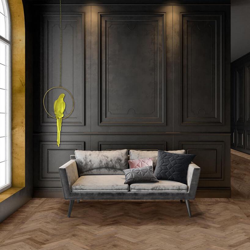 szara sofą na tle ciemnej ściany na drewnianej podłodze