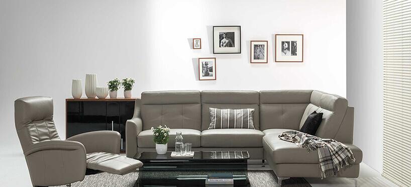 beżowa rogówka ifotel zpodnóżkiem czarny stolik na tle białej ściany