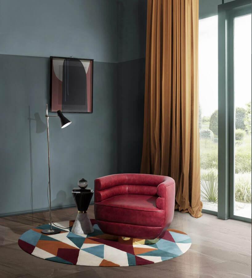 czerwony fotel na dywanie wtrójkąty na brązowej podłodze na tle zielonych ścian