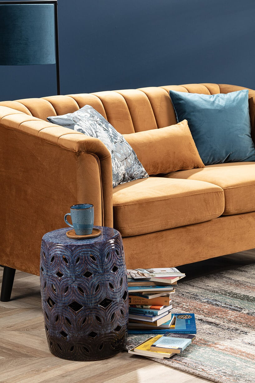 jasno brązowa kanapa zpuszystymi poduszkami wciemno szarym pomieszczeniu