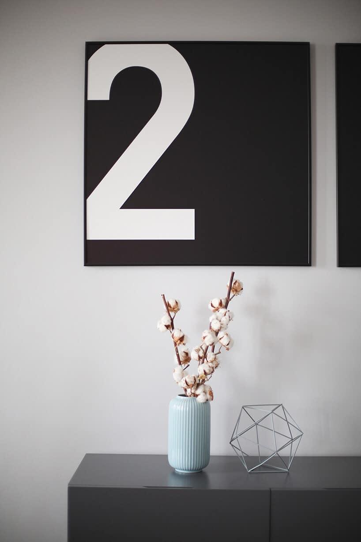 cyfra dwa nadrukowana na czarnym metalowym elemencie zawieszonym na szarej ścianie