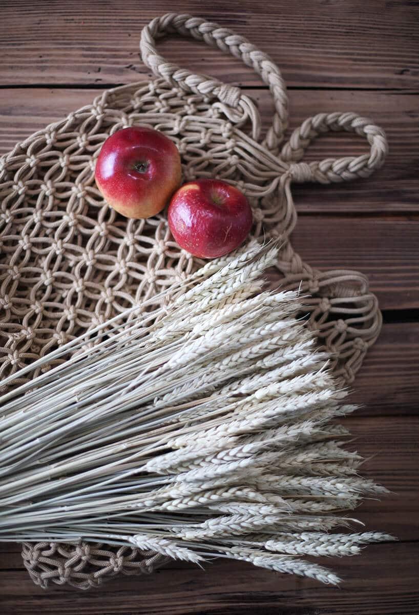drewniany stół zdesek zdwoma czerwonymi jabłkami leżącymi na szarej robótce drucianej
