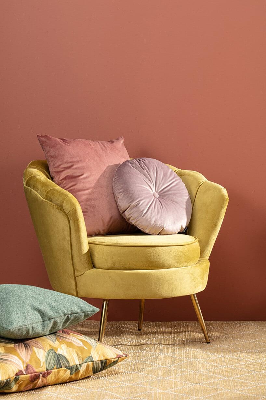 okrągły fotel wkolorze jasnej żółci zdwoma poduszkami wkolorach różu na tle lekko czerwonej ściany