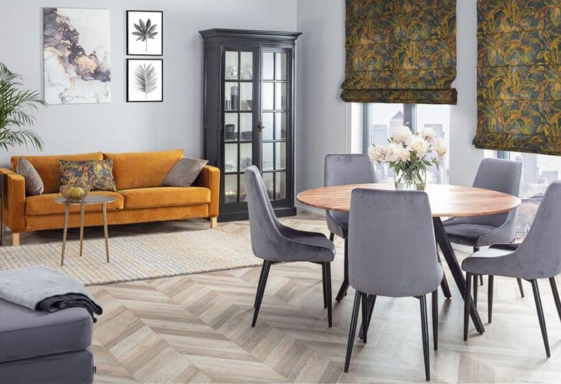 pomieszczenie zmusztardową kanapą oraz podłoga zklepek iroletami rzymskimi zmotywem kwiatowym