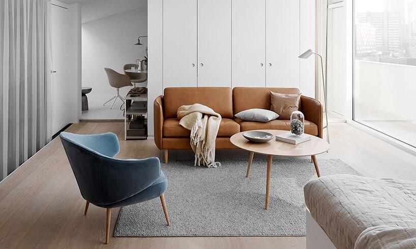 nowe meble zstarym stylem na drewnianych zaokrąglonych nogach wpomieszczeniu zbiałymi szafami oraz dużymi oknami