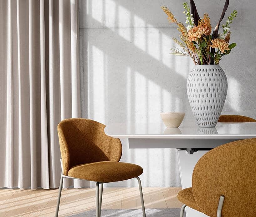 dwa brązowe krzesła zmetalowymi nóżkami przy artdeco stole zdużym zdobionym wazonem