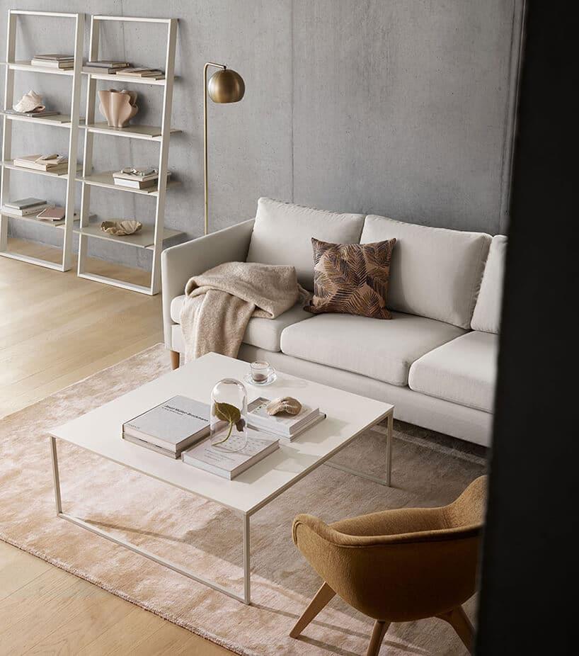 kremowa kanapa na jasnej ebowej podłodze obok metalowego regału na książki